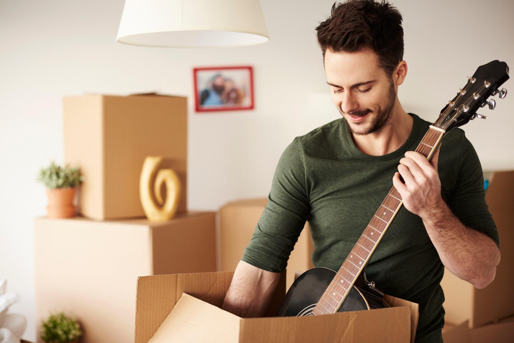 Mann packt Gitarre aus