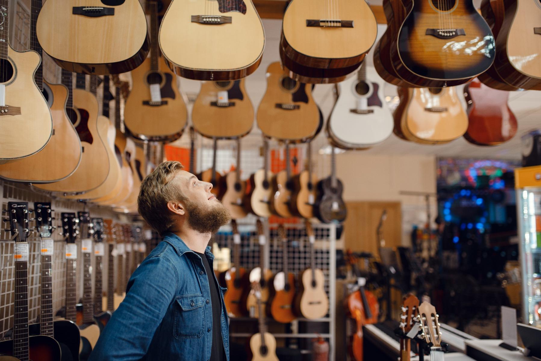 Ein Mann sucht sich eine Gitarre aus