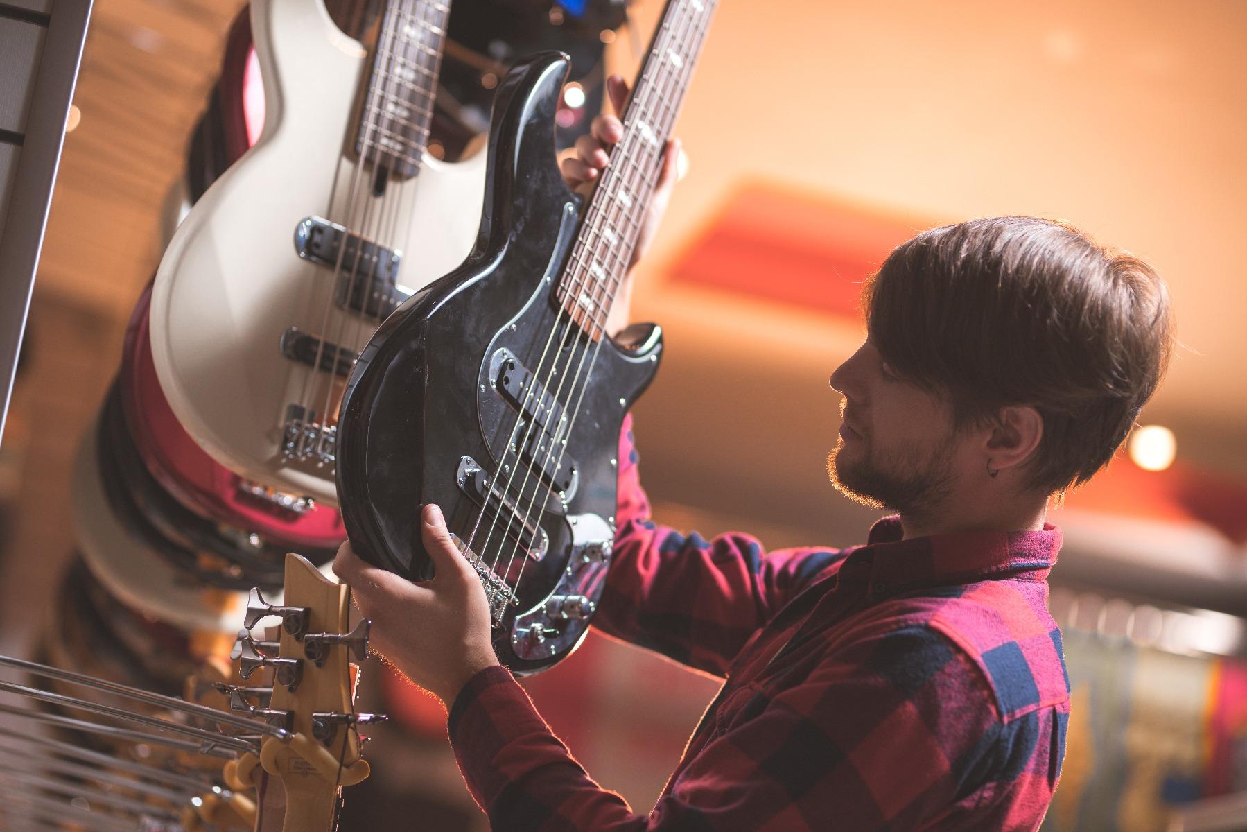 Mann sieht Bassgitarre verliebt an